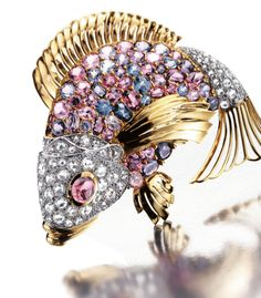 GEM-SET AND DIAMOND BROOCH, SEAMAN SCHEPPS.  Designed as a fish, the scales set with multi-coloured spinels, the head pavé-set with rose-cut diamonds, to a cabochon garnet eye, mounted in yellow and white gold,  signed Seaman Schepps and numbered, maker's marks.