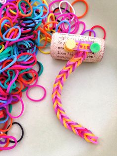 DIY fishtail loom 1. Take a wine cork (or any cork). 2. Put Something that will hold the bands. 3. Start looming <3