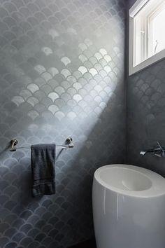 Modern gray bathroom features walls clad in gray metallic fish scale tiles.