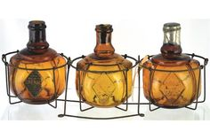 SET OF FIRE GRENADES IN WIRE CAGE. 15ins long, amber glass spherical shape, embossed within diamo