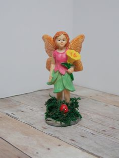 Fairy Garden Fairy Resin - Flower. This fairy is perfect for any whimsical garden! She stands about 5 inches tall and is holding a yellow flower. Her feet are in real dried moss with a mushroom popping out from below.
