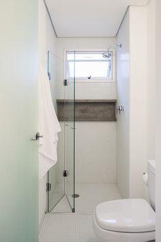 Assim como o piso do banheiro, o box foi revestido de pastilhas. A área de banho tem porta camarão e um nicho de concreto para acomodar os itens de higiene. O projeto de reforma do apartamento em São Paulo (SP) é assinado pelo Grupo Garoa Arquitetos