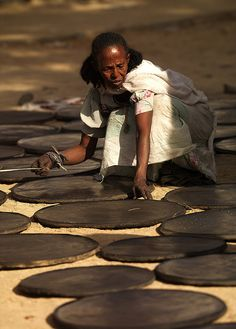 Woman making injera plates, Keren market, Eritrea. Injera is a yeast-risen flatbread with a unique, slightly spongy texture. Traditionally made out of teff flour, it is a national dish in Ethiopia and Eritrea.