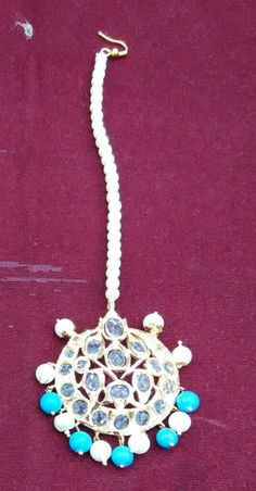 Nizam Jadavi Tika - This is a maang tika studded with gemstones and a pearl string. Choice of pearls like cream, off white, etc., semi precious stones like emerald, turquoise, etc. and many  styles available. For custom orders please contact 408-800-7134