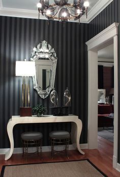 The subtle and stylish black on black stripes on the wall add height visually, and they are about the only subtle element in this space. Black and white color combos are often designed to create a bold yet timeless look and this well designed space does not disappoint.