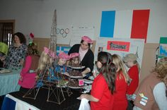 cute France booth (like how someone made the girls little berrets to wear, and they did a 'craft' coloring sheet of a shield w/a fleur de lis...served homemade bon bons, but I'm not sure we can have food...will check on this.  I like the simple French flag out of posterboard.  My mom has a wire Eiffel tower statue that we can use, though it's much smaller.  I've also got several books re: France to have for display.