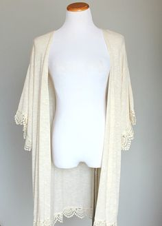 Gorgeous cream lightweight knit kimono features quality crochet detailing along hems. Knee-length kimono has an oversized, relaxed, and super soft fit. Our favorite knitted crochet kimono! Looks amazing with highwaisted shorts and a crop top.    MADE IN USA
