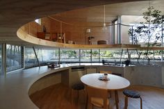 circular kitchen, half set below ground, plywood mezzanine loft above.
