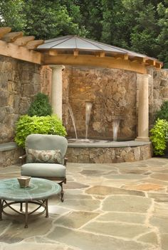 A discreet corner hot tub/spa, fed by cascading fountains, is surrounded by rock walls and covered with a roofed pergola in this beautiful backyard oasis - rugged-life.com