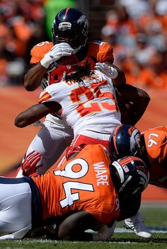 Running back Jamaal Charles (25) of the Kansas City Chiefs is tackled by strong safety T.J. Ward (43) of the Denver Broncos, defensive end DeMarcus Ware (94) of the Denver Broncos and defensive end Malik Jackson (97) of the Denver Broncos. The Denver Broncos played the Kansas City Chiefs at Sports Authority Field at Mile High in Denver, Colorado on September 14, 2014. (Photo by AAron Ontiveroz/The Denver Post)-- #ProFootballDenverBroncos