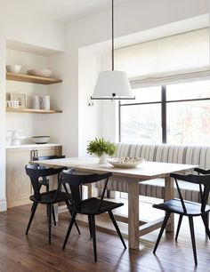 Light wood dining table surrounded by sleek black chairs under a white drum hanging light. A striped upholstered dining bench features gray and blue fabric against a dining room window fitted with a linen roman shade.