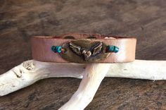 Celebrate Fall with this unique, handmade leather cuff. This bracelet features a bronze winged heart accented with turquoise gemstone beading.