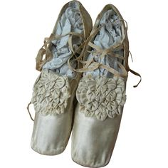 A very beautiful, if somewhat timeworn pair of early Victorian (circa 1810 - 1820) ecru silk wedding shoes with beautiful rosettes embellishing the