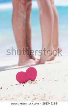 Barefoot female legs standing up tiptoe on man's foots on beach with turquoise sea background, decorated pink heart object.  Romantic honeymoon vacation concept - stock photo
