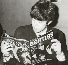 Beatle Paul McCartney reading a magazine about the Beatles! Circa early 1960's