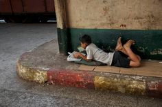 MYANMAR. January 2014. A boy lies on the sidewalk and reads. by Steve McCurry