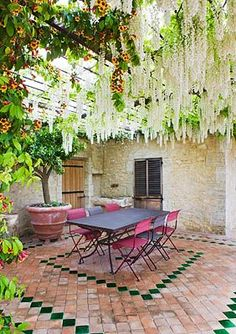 Beautiful patio or courtyard. Look like white wisteria is dripping through the pergola.