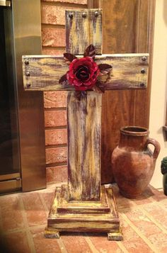 Beautiful rustic wooden cross measuring approximately 22x12x8. Has an old world look in tones of brown, red, cream, tan, and gold. Centered on