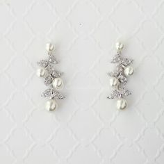 These bridal drop earrings are embellished with CZ covered leaves and lovely off-white pearls in a wonderful vine design. Elegant yet relaxed, they are perfect for an bride or special occasion.