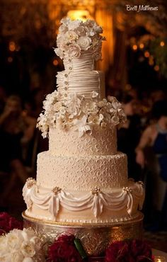4 Tier cream wedding cake with draping on the side and silk flowers on the top between layers.
