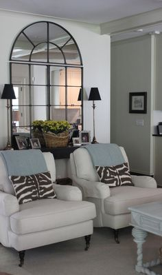 Love the mirror and chairs with matching pillows and throws.