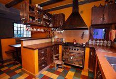 Esta cocina es dueña de múltiples detalles. La madera contrasta con el metal del horno y de las manijas. El piso es calcareo colorido