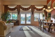 Window Treatment Ideas: Large windows with transoms and a French door.  One huge cohesive treatment; swag valances and jabots.