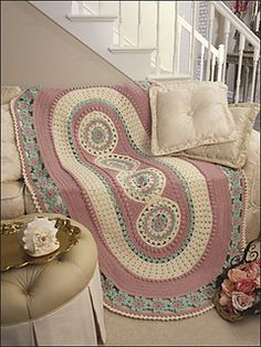 Generously-sized afghan with a center panel of floral motifs and add textured borders with an edged ring of pretty flower.
