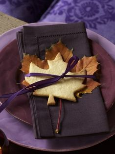 Very pretty idea for a fall dinner party...sugar cookie in the shape of a maple leaf on top of a real (or realistic fake) maple leaf tied to a linen napkin with a pretty ribbon. Lots of color and leaf variations to consider...even a holly-leaf-shaped cookie and holly or other evergreen greenery for the Christmas holidays.