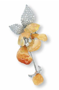 A FIRE OPAL AND DIAMOND CLIP BROOCH  Designed as an orchid, the petals set with five carved fire opals, enhanced by brilliant-cut diamond pistils and leaves, joined to the pavé-set diamond stem and a fire opal terminal, mounted in 18k white gold