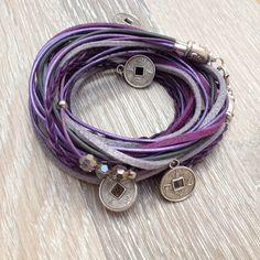 Veter wrap armband in paars met grijs met 3 maal 3 grijs 6mm kristallen op een veter vast gezet en 5 Chinese geluksmuntjes in de gevlochten veters. Geschikt voor een pols van ~17cm. Te koop bij JuudsBoetiek voor €12,50. Voor bestellen mail naar juudsboetiek@gmail.com. #veter #wrap #armband #geluksmuntje
