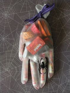 Halloween treat hand. Used surgical gloves. You can find them at Walgreens, Walmart, Rite-Aid. For the fingers I used Smarties. Then I filled them rest of the way with mini Hershey candy bars and mini Reeses peanut butter cups, and Hershey Kisses. I had to add a little ring. Once filled, I just tied them with craft ribbon. Easy peasy.