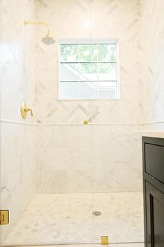 This marble clad seamless glass shower features A gold shower kit mounted to marble herringbone wall tiles framing a window positioned above marble pencil tiles lining lower wall marble tiles complementing marble hexagon floor tiles.
