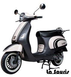 Deze Vespelini Scooter in Mat Zwart / Wit is door La Souris zelf ontworpen. Dit houdt in dat deze scooter nergens anders verkrijgbaar is. De scooter is voorzien van een halogeen koplamp, geïntegreerde knipperlichten en Led Remlicht. Dit model lijkt veel op de Vespa LX. De scooter wordt geleverd met een gratis chromen bagagerek, chromen charterkap en white wall banden t.w.v. € 150,00.
