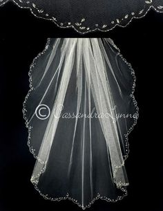 A fabulous scalloped wedding veil with a seed bead edge and crystal bead accents. It is 36 inches long and 72 inches wide, on a four inch metal comb. This veil