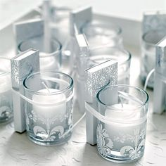Snow White Theme, Light the Way, Do your guests a favor and offer a to-go gift that's both functional and fanciful. Votive glasses—embellished with laser-cut vinyl transfers you can customize—are paired with silver-embossed matchboxes; a thin strip of satin ribbon ties everything together.%0A Votive holders (with white damask pattern), Wonderful Graffiti Wedding; matches, foryourparty.com; paper tray liner, Outwater LLC.