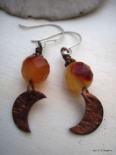 Copper crescent moons made from bench scraps dangle from the bottom of faceted carnelian beads. The beads are multicolored from a light orange to a brownish color. The elements are wire wrapped together with a copper wire and hang from sterling silver ear wires. The entire length of the earring from the top of the ear wire to the bottom of the moon is about two inches. The moon is about a half inch in length and has been hammered to give it texture.