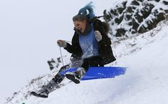 Bethany Thompson takes off on her sledge after snow fell in Bradgate Park near Newtown Linford #England