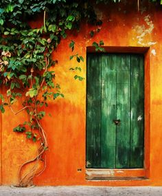 Green door in the historic center of Cartagena, Colombia. Tangerine wall