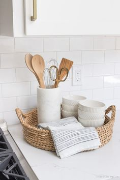 The perfect set-up for next to your range! A round woven tray holds most-used utensils in a pretty marble holder, a hand towel, and white patterned bowls! #kitchen #kitchens #kitchenrenovation #kitchendesign #kitchenideas