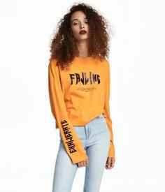Orange. Etwas verkürztes Shirt aus bedrucktem Jersey. Modell mit leicht überschnittenen Schultern und Langarm.