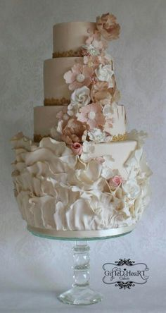 A beautiful four tier wedding cake with fondant ruffles and sugar paste flowers in colors of pink and white