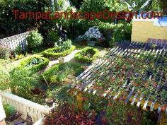 TampaLandscapeDesign Classic English garden with pergola, climbing roses, honeysuckle, rose parterre, folly fountain and herb garden.