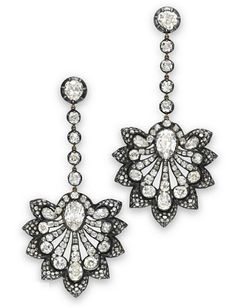 A PAIR OF DIAMOND EAR PENDANTS   Each suspending an old mine-cut diamond pierced plaque, centering upon an inverted pear-shaped old mine-cut diamond, extending a graduated fan of old mine-cut diamonds trimmed by rose-cut diamonds, from a line of collet-set old mine-cut diamonds, to the bezel-set old mine-cut diamond surmount, mounted in silver-topped gold. Victorian or Victorian style.
