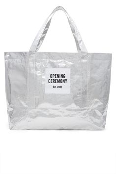 Opening Ceremony, Large Metallic Silver Tote Bag OC's signature blue and red shopping totes are reimagined in heavy-duty yet lightweight polypropylene. Featuring a striking crinkled metallic finish, this tote comes with OC's classic box logo patches along the front and back. It's perfect for grocery runs, as a waterproof beach bag, or any of your travel needs., OC EXCLUSIVE, Secure top zipper closure, 100% polypropylene, Imported