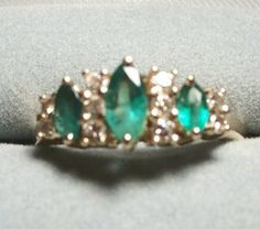 http://www.ebay.com/itm/150954695798  TEN GENUINE FULL-CUT ROUND DIAMONDS surround and highlight the rich green marquise cut emeralds. In REGENCY STYLE, the prong-set stones elevate the gemstones to a crown shape, highlighting the GENUINE EMERALDS in a traditional tapered band setting. The MARQUISE CUT gemstones are AMAZING, Irish green, well matched, and beautifully cut.