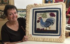 Trudi Aprile holding a McAdoo Rugs Rooster design.