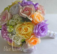 Descrição do Produto  Rosas multicores e folhagens - arranjados com harmonia e graça - este elegante buquê de noiva é perfeito para o seu casamento.  Detalhes do Buquê  - Rosas lilás / salmon / amarela /pink de Seda - Rosas cor rosa - Toque Natural - Mini rosas verdes - Fitas de cetim branca envolve a haste do buquê - Laço Bailarina de organza lilás - Pérolaa acentuam a haste do buquê  Medidas - Tamanho grande:- 28 cm de largura x 28 cm de altura   Este buquê está disponível a Pronta Entrega…