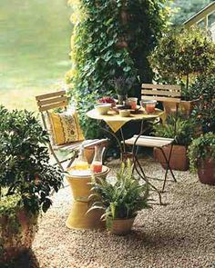 A charming pea-gravel breakfast patio furnished with a cafe table, matching chairs, and a sunflower-yellow linen brings to mind alfresco dining in the South of France. A pillow in coordinating fabric adds to the effect. Our ice bucket is made of stacked flowerpots (the one at the base is upside down; water easily drains out the bottom). Edible kumquats underplanted with chartreuse-colored moneywort conjure a relaxed air. The specimens are grown in ceramic containers with an amber glaze…