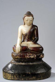 Buddha Maravijaya assis en vajrasana sur un socle lotiforme vêtu d'une robe monastique rabattu en un pli sur la poitrine lui découvrant l'épaule droite et coiffé de fines bouclettes surmontée de la protubérance cranienne ushnisha.  Marbre partiellemnt laqué et doré.  Birmanie.  Mayong.  Royaume des Etats Shan.  18 ème siècle.
